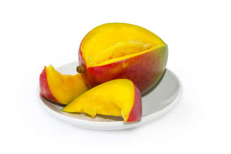Partly cut ripe mango fruit on saucer on a white background