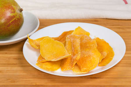 Dried slices of mango pulp on white dish against fresh whole mango on saucer on a wooden surface, close-up