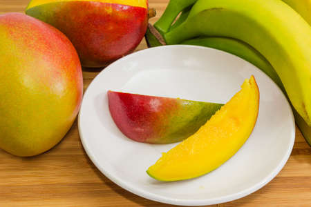 Slices of ripe mango fruit on saucer among the other mango and bananas on a wooden surface