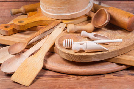 Pile of various kitchen utensils made with different natural wood type on an old rustic table Foto de archivo