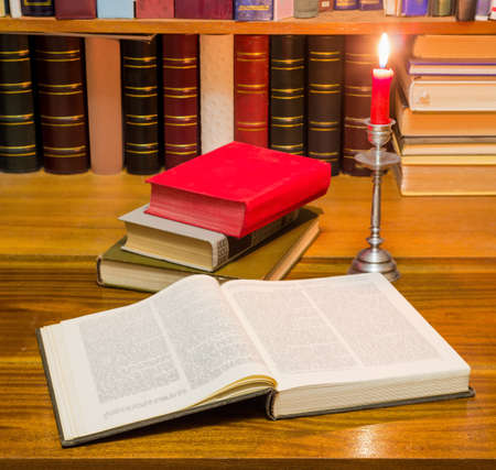Open old big book with a blurred text on a wooden table against the background of shelf with other books by candlelight