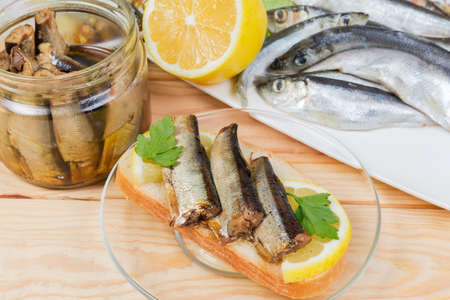 Open sandwich with smoked sprats preserved in vegetable oil and lemon slice against of some ingredients on a rustic table, close-up in selective focus