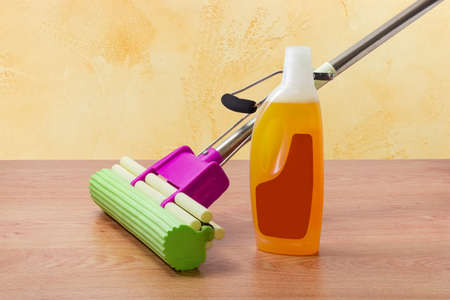 Mop with green sponge and mounting clamp, plastic bottle of liquid floor cleaner on a wooden floor 版權商用圖片