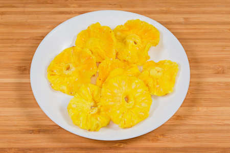 Dried slices of pineapples in the form of circles on white dish on a wooden surface 版權商用圖片