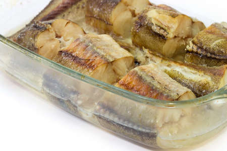 Baked pieces of the hake in the glass pan for baking on a white background, fragment close-up in selective focus 版權商用圖片