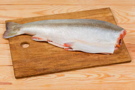 Whole carcass of the fresh gutted uncooked arctic char without head on the wooden cutting board on rustic table