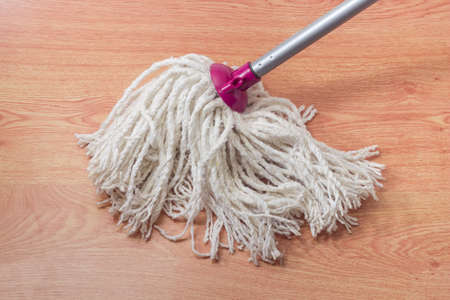 Bottom working part of classic yarn mop in the form of bundle of cotton rope segments on a wooden floor