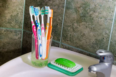 Different toothbrushes in a stand on sink on a background of wall in bathroom covered with green tile