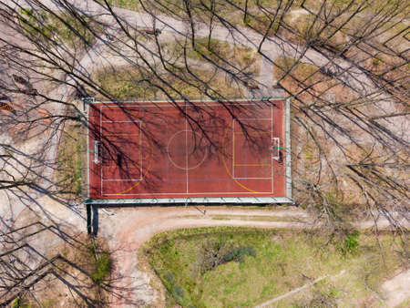 Universal outdoor sports field with red absorbing coating and color markings for playing various sports among the trees of the park in early spring, vertical aerial view