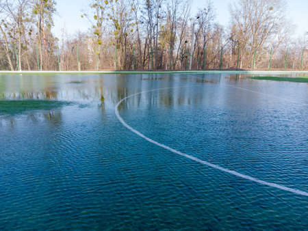 Fragment of school soccer field drenched with melted water from sudden melting snow in early spring