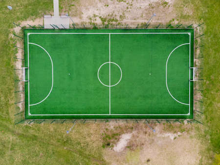 Outdoor mini football field with fence and street lights located among lawn in springtime, vertical aerial view Standard-Bild