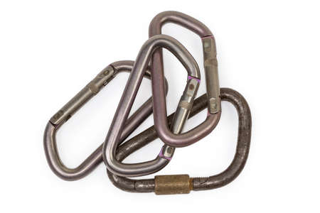 Vintage steel locking triangular shape carabiner with straight screw gate and several oval titanium non-locking carabiner with sprung solid gates on a white background, top view