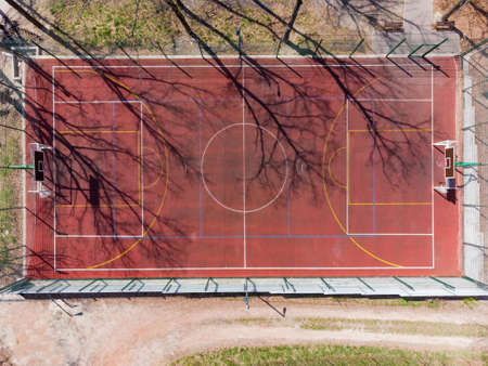 Universal outdoor sports field with red absorbing coating and color markings for playing various sports in park in springtime, vertical aerial view close-up