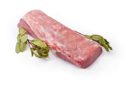 Piece of cooled raw pork loin and twigs of dried bay leaves on a white background