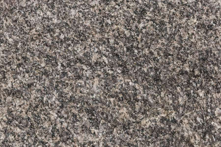 Unprocessed rough torn edge of stone gray granite with pronounced granular structure outdoors, texture, background Stock Photo