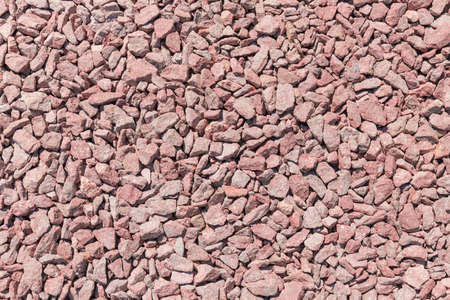 Small section of the ground covered with gray-red granite rubble outdoors, top view close-up Stock Photo