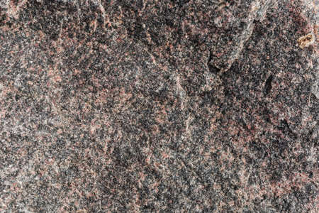 Unprocessed rough torn edge of stone black-red granite outdoors, texture, background