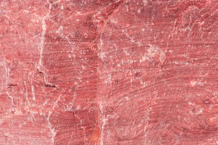 Unprocessed rough torn edge of stone red granite with slightly layered structure, covered with several small cracks outdoors, texture, background