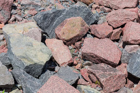 Section of placer of stones gray and red granite different sizes outdoors in summer day Stock Photo