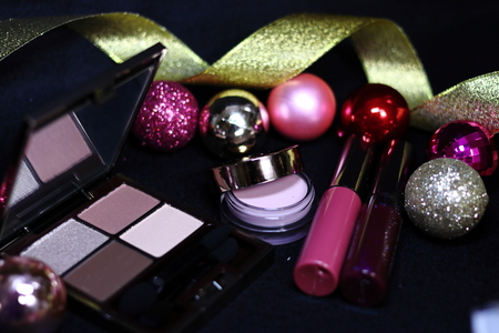 Cosmetics of eye shadow, highlight, lipstick and colorful Christmas decorations on black background 免版税图像