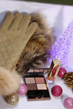 Pink and gold decoration with Christmas tree with cosmetics (eye shadow and lipstick) and fur stalls and gloves (white background)