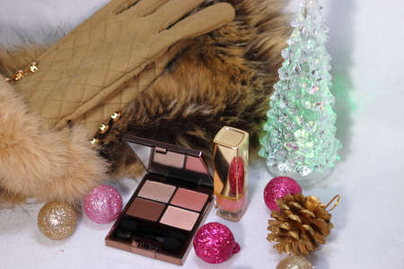 Pink and gold decoration with cosmetics (eyeshadow and lipstick) and watch and fur stoles and gloves and Christmas tree (white background)