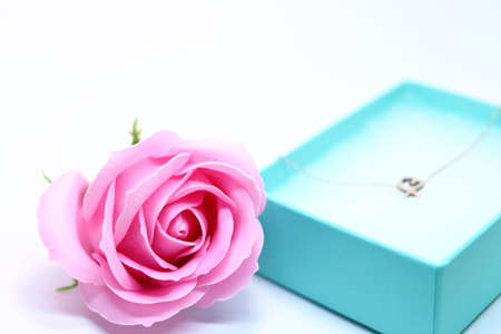 Heart necklace and pink rose in gift box Imagens