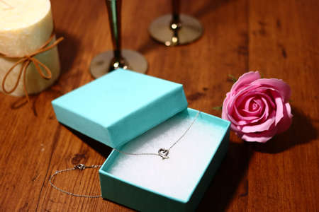 Necklace presents, wine glasses, roses and candles Imagens