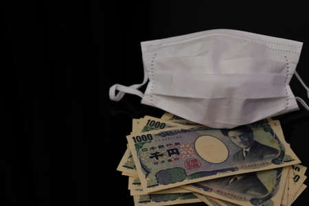 Japanese money and white mask placed on the table