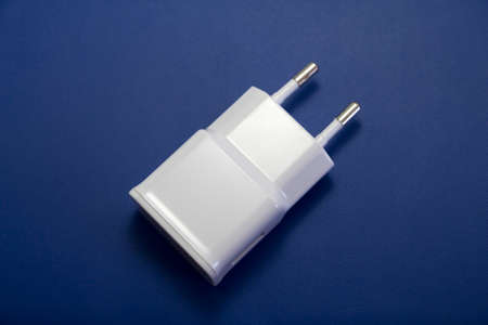 ac: AC power supply adapter on blue  leather background. Stock Photo