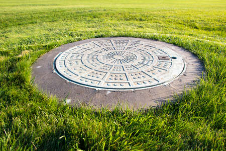 Metal manhole in a background of green grass on the field.