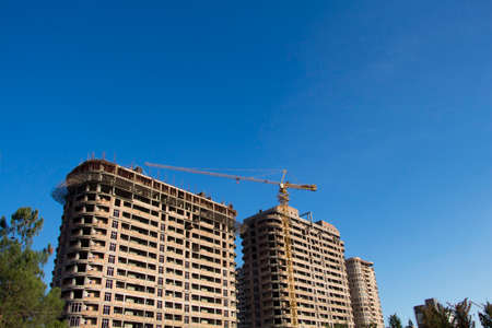 High-rise building construction site with crane against blue sky Stock Photo