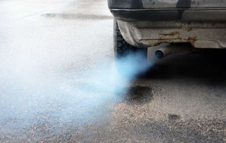 Gases emitted from the exhaust pipe dark old car, standing on the pavement. Stock Photo - 136526319