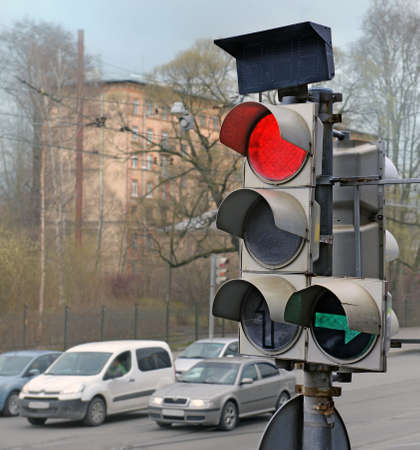 Traffic light on red and a green arrow against the street. Blur cars awaiting passage permitting signal. Banco de Imagens