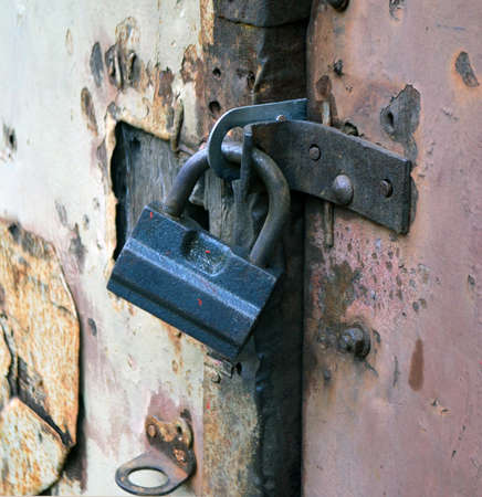 The mechanical hinged lock on old crumpled of a door of garage.