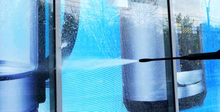 washing of a glass show-window of household shop by a water stream under a high pressure