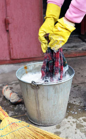The woman's hands in yellow rubber gloves who washes a floorcloth in a metal bucket with soap water
