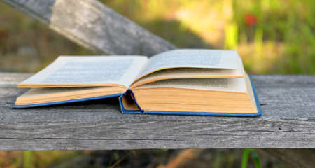 The old repeatedly read open book with hard shabby, blue cover and  turned yellow edges of pages lies on a wooden bench in a garden.