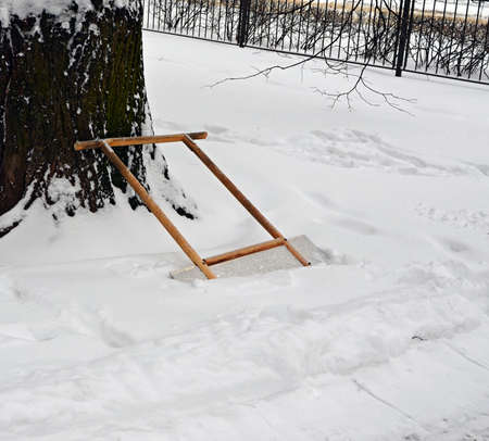 Scraper for remove snow is leaned against a trunk of a big tree in a snowdrift near the cleared-away path during snowfall on background of garden fencing.
