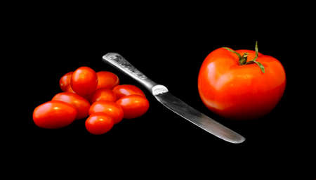 One big tomato, heap of small tomatoes and knife between them on a black background. Size and quantity as concept of the competition Banque d'images
