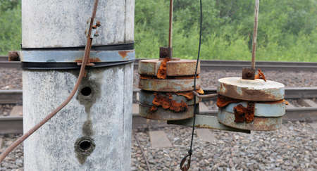 Fragment of compensating device of railway contact system against railway tracks. Garlands of freights.