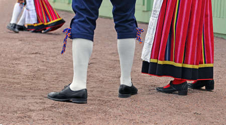 Legs of man and woman, who are dressed in traditional Estonian clothing. They look at dancing couple and are going to dance too.