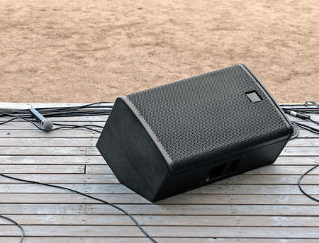 Concert speaker system, wires and microphone on the stage with old wooden floor outdoor.