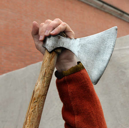 Hand of man leaning on  old battle broadaxe.Axe before  hand.Vikings widely used such weapon.