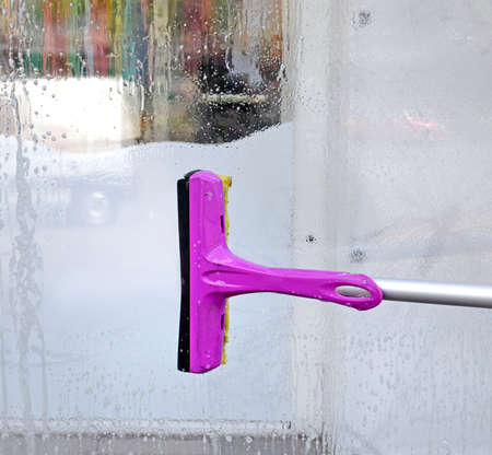 Washing of a show-window. The brush cleans the glass of water and soap foam. The image can be used as a background.