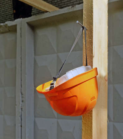Orange hard hat hangs on the nail hammered into wooden scaffolding against of a concrete wall, fencing the building site