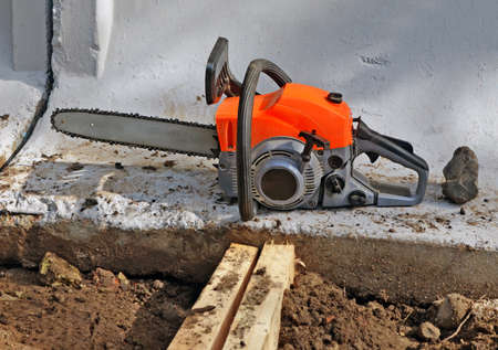 The chainsaw covered with sawdust at the bottom of a concrete wall fencing the building site Stok Fotoğraf