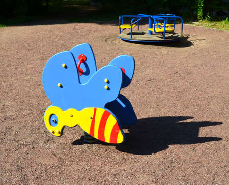 Playground equipment. swing in the foreground and a roundabout on the back
