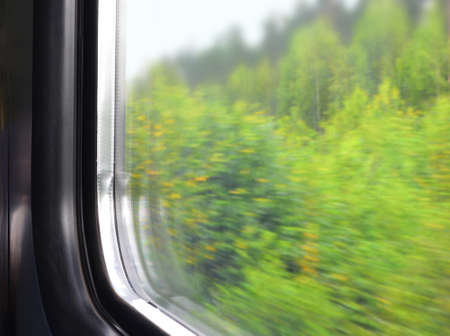 Part of a window of a moving electric train. the autumn wood which blurred because of movement speed behind double glass of a window Standard-Bild