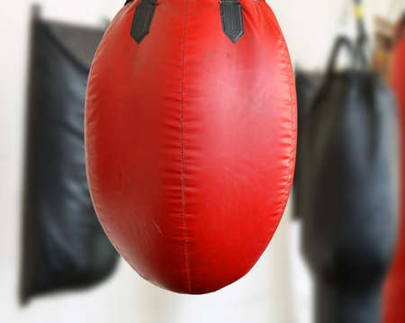 Red beat-up a punching bag hangs in a gym near white wall among other punching bags. blurred background.